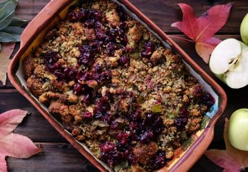apple and raspberry crumble surrounded by maple leafs on rustic table