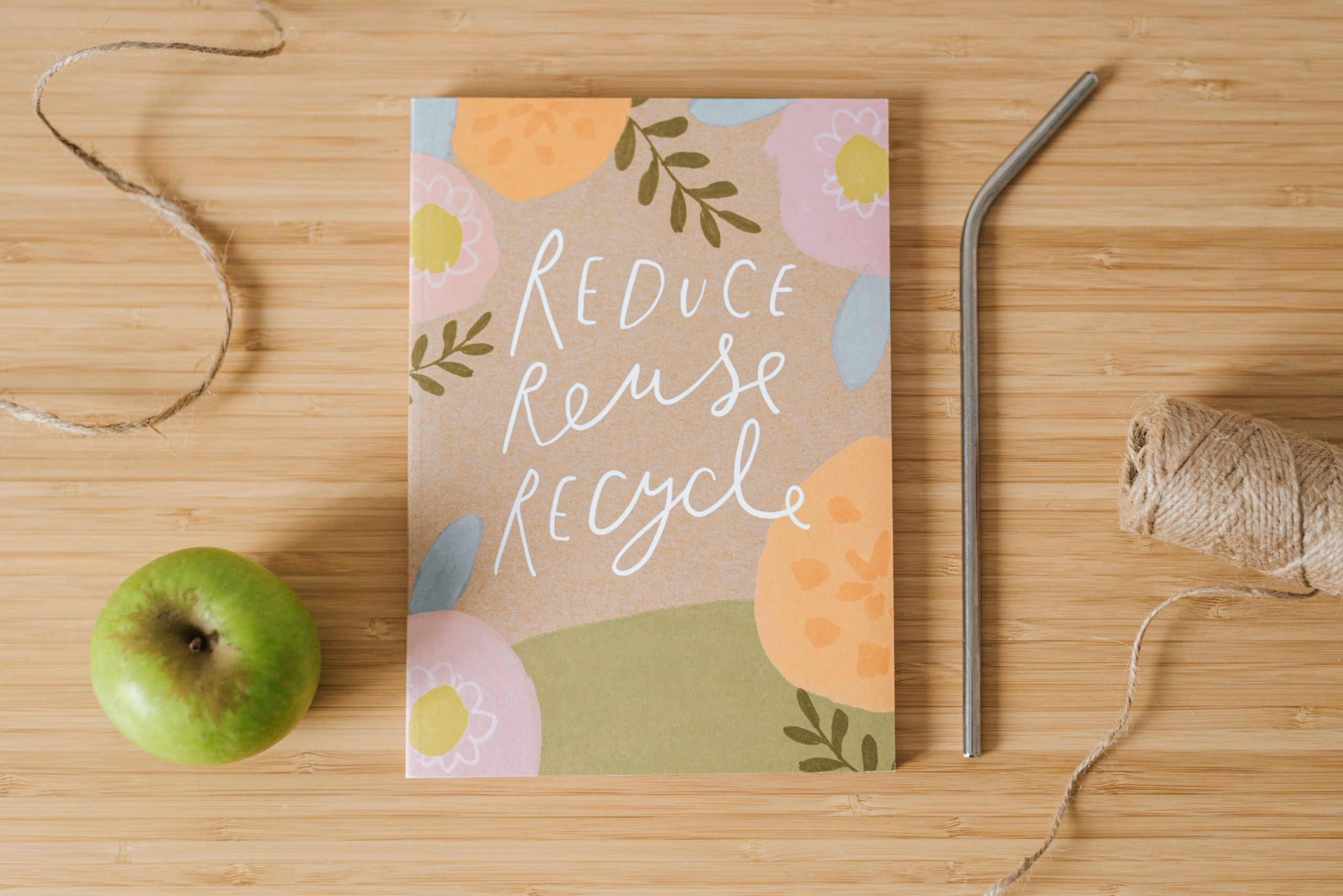 common items that can be reused and a notebook that says reduce, reuse, recycle